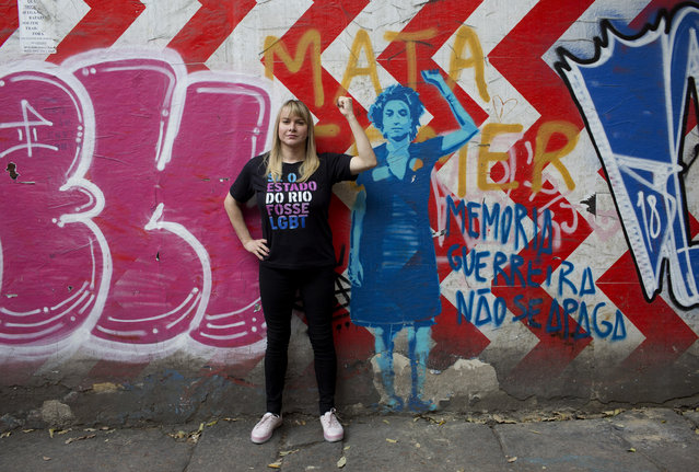 In this September 20, 2018 photo, Barbara Aires, 35, poses for a photo next to a mural of slain councilwoman Marielle Franco, in Rio de Janeiro, Brazil. Aires is one of 53 transgender candidates running for state and federal offices in Brazil, a deeply conservative and religious country that is also one of the most dangerous in the world for transsexuals. (Photo by Silvia Izquierdo/AP Photo)
