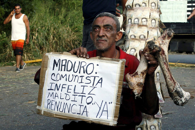 "A man holds a bone and a placard that reads ""Maduro: communist, unhappy, damn. Resign, now"", in front of a pole covered with 100-bolivar bills during a protest in El Pinal, Venezuela, December 16, 2016. (Photo by Carlos Eduardo Ramirez/Reuters)"