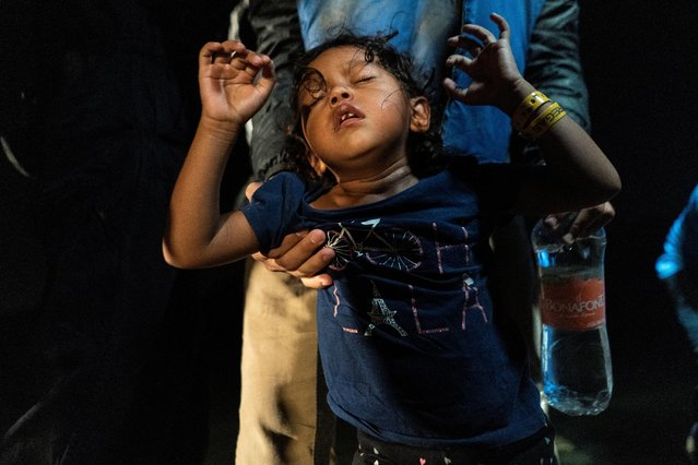 An asylum-seeking migrant child from Honduras reacts as disembarking an inflatable raft after crossing the Rio Grande river into the United States from Mexico in Roma, Texas, U.S., June 8, 2021. (Photo by Go Nakamura/Reuters)