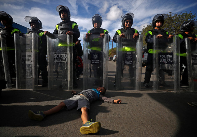 Fernando Velosque, a six-year-old migrant boy from Honduras, part of a caravan of thousands from Central America trying to reach the United States, lies on the floor in front of Mexican riot police as migrants gather outside the El Chaparral port of entry of border crossing between Mexico and the United States, as seen from Tijuana, Mexico, November 22, 2018. (Photo by Hannah McKay/Reuters)