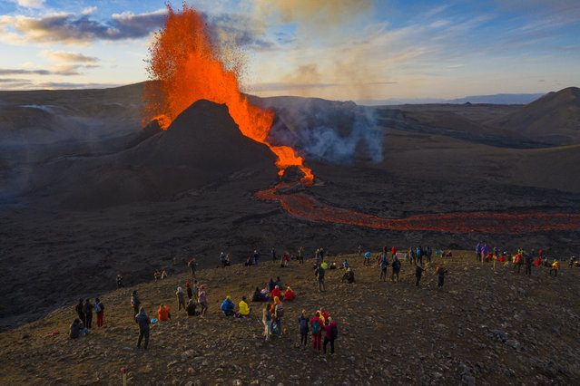 People watch as lava flows from an eruption from the Fagradalsfjall volcano on the Reykjanes Peninsula in southwestern Iceland on Tuesday, May 11, 2021. The glow from the bubbling hot lava spewing out of the Fagradalsfjall volcano can be seen from the outskirts of Iceland's capital, Reykjavik, which is about 32 kilometers (20 miles) away. Pandemic or no pandemic, the world will never stand still. That's perhaps no clearer than in Iceland where the Fagradalsfjall volcano has awoken from a slumber that has lasted 6,000 years, give or take a year or two. (Photo by Miguel Morenatti/AP Photo)