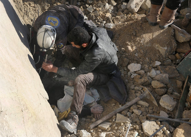 Syrian rescuers remove a victim from under the rubble following a reported air strike on the rebel-held neighbourhood of al-Kalasa in the northern Syrian city of Aleppo, on February 4, 2016. (Photo by Thaer Mohammed/AFP Photo)