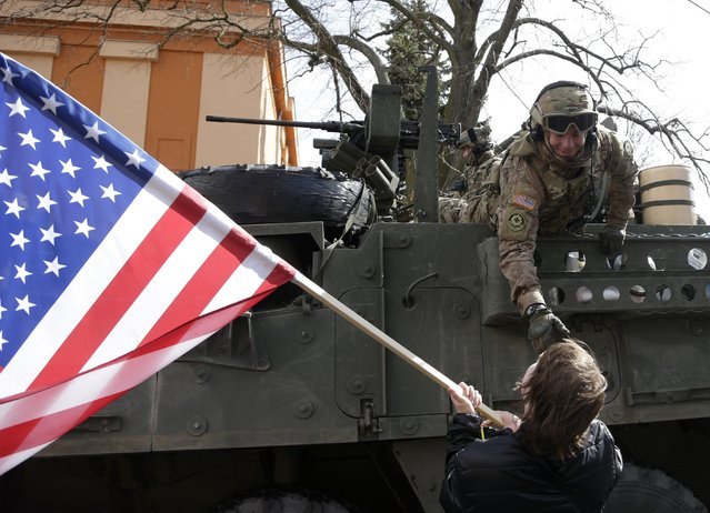 A US army soldier greets a supporter as a US army convoy arrives in Prague, Czech Republic, Monday, March 30, 2015. (Photo by Petr David Josek/AP Photo)