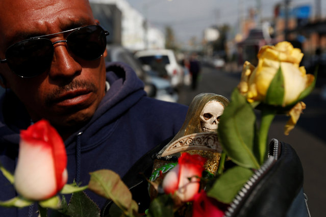 A man carries a figurine of Santa Muerte or The Saint of Death during the first prayer of the New Year in Mexico City, Mexico January 1, 2017. (Photo by Carlos Jasso/Reuters)