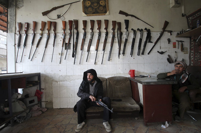"A ""Free Syrian Army"" fighter inspects a weapon inside a gun shop in Duma neighbourhood in Damascus, November 24, 2013. (Photo by William Ismail/Reuters)"
