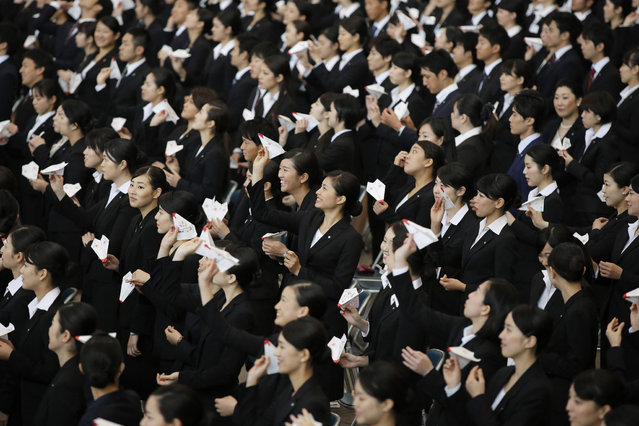 Japan Airlines Co. (JAL) group companies' new employees practice before releasing paper planes during an initiation ceremony at the company's hangar near Haneda Airport in Tokyo, Japan, on Wednesday, April 1, 2015. A report showed the unemployment rate in Japan fell to 3.5 percent in February, matching economist estimates and declining from 3.6 percent the previous month. The jobs-to-applicants ratio increased to 1.15, the highest reading in 23 years. (Photo by Kiyoshi Ota/Bloomberg)