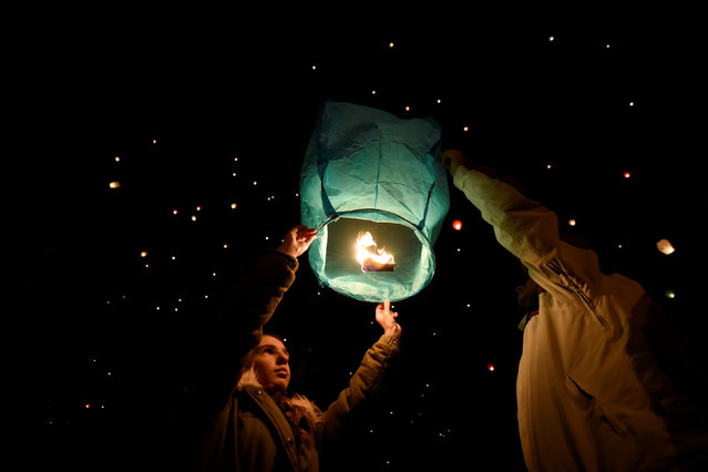 People prepare to release a sky lantern during Christmas festivities in Volos, Greece, December 26, 2018. (Photo by Alexandros Avramidis/Reuters)