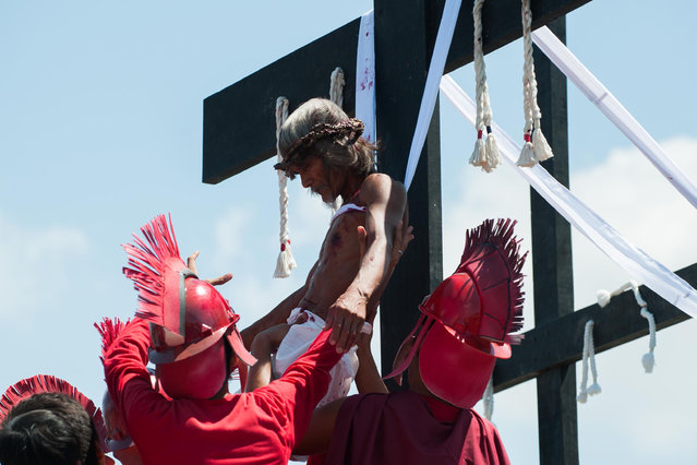 A Catholic devotee nailed to a cross is helped by participants during a reenactment of the crucifixion of Christ on Good Friday on April 3, 2015 in San Pedro Cutud village in Pampanga province, Philippines. (Photo by Dondi Tawatao/Getty Images)