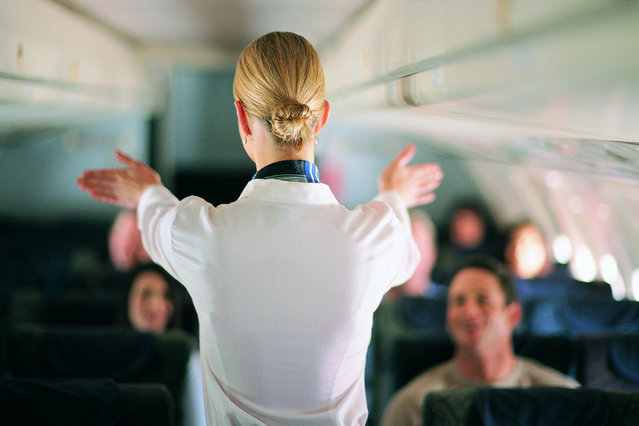 Rear view of air stewardess explaining aeroplane safety to passengers. (Photo by James Lauritz/Getty Images)