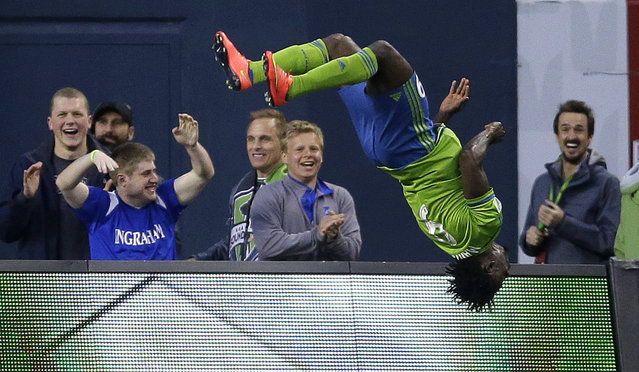 Seattle Sounders' Obafemi Martins flips after he scored a goal against the Houston Dynamo as fans – including former Sounder Roger Levesque, right – cheer in the first half of an MLS soccer match, Saturday, April 4, 2015, in Seattle. (Photo by Ted S. Warren/AP Photo)