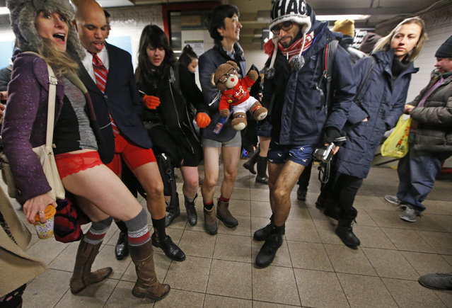 A passerby, far right, glances as participants in the 16th annual No Pants Subway Ride pose for photographs in their underwear, Sunday, January 8, 2017, in New York after riding pantless in the subway. (Photo by Kathy Willens/AP Photo)