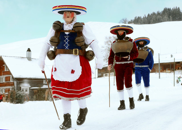 """Men dressed as """"Chlaeuse"""", figures that scare away evil spirits, carry round bells and cowbells as they walk on a snow-covered road during the traditional """"Sylvesterchlausen"""" near the northeastern village of Urnaesch, Switzerland January 13, 2017. (Photo by Arnd Wiegmann/Reuters)"""