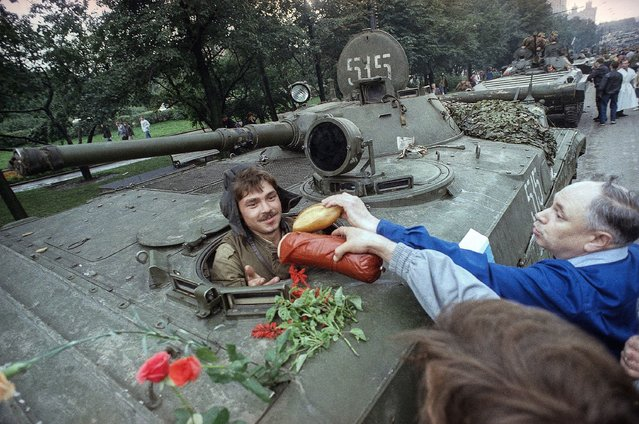 In this Wednesday, August 21, 1991 file photo, appreciative muscovites hand bread, sausages and flowers to a Soviet tank's driver who helped stop the failed hardline coup in Moscow, Russia. When a group of top Communist officials ousted Soviet leader Mikhail Gorbachev 30 years ago and flooded Moscow with tanks, the world held its breath, fearing a rollback on liberal reforms and a return to the Cold War confrontation. But the August 1991 coup collapsed in just three days, precipitating the breakup of the Soviet Union that plotters said they were trying to prevent. (Photo by Czarek Sokolowski/AP Photo/File)