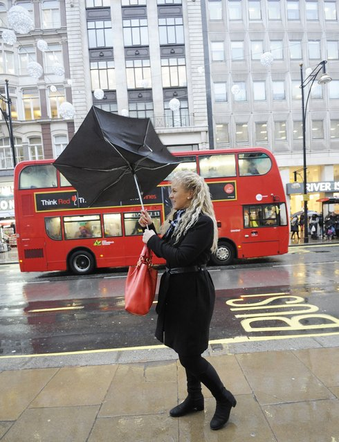 A woman shopper falls victim to the windy weather along Oxford Street in London's West End  23 December 2013. (Photo by Facundo Arrizabalaga/EPA)