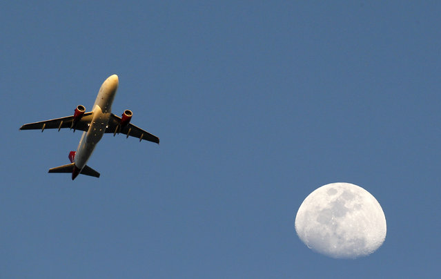 Virgin Atlantic Airlines crosses the Waxing Gibbous moon as it approaches Los Angeles International Airport in Whittier, Monday, March 30, 2015. (Photo by Nick Ut/AP Photo)