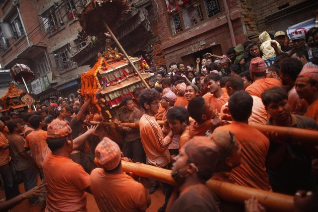 Nepalese devotees, covered in color vermilion powder, carry a palanquin with idols of Hindu deities during Sindur Jatra festival in Thimi, outskirts of Kathmandu, Nepal, Wednesday, April 15, 2015. (Photo by Niranjan Shrestha/AP Photo)