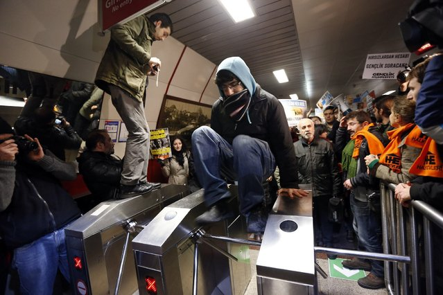 A demonstrator jumps over a turnstile during a protest against private security guards at Taksim metro station in central Istanbul December 31, 2013. Hundreds of left-wing demonstrators gathered at Istanbul and Ankara main metro stations to protest against private security guards working at metro stations. Aykut Kelek, a 20-year-old man, who attempted to board the metro without paying in Istanbul was beaten by a security guard and hospitalized on Monday, local media reported. (Photo by Murad Sezer/Reuters)