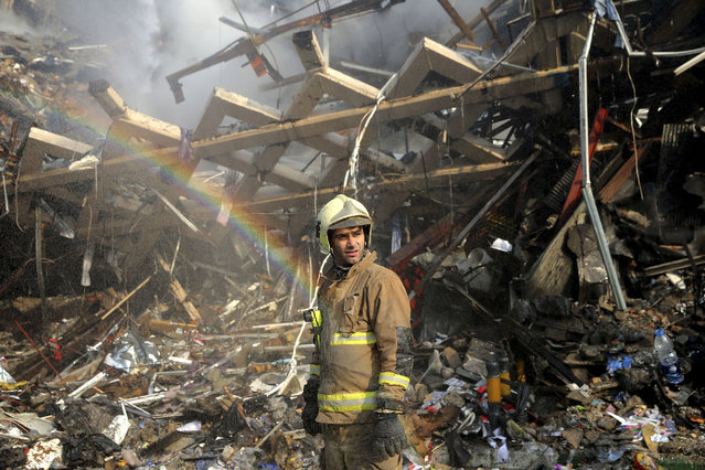 A rainbow appears as a firefighter removes debris of the Plasco building which was engulfed by a fire and collapsed on Thursday, in central Tehran, Iran, Friday, January 20, 2017. Scores of workers and dozens of trucks were searching the ruins Friday, a day after a historic high-rise building in the heart of Tehran caught fire and later collapsed. (Photo by Ebrahim Noroozi/AP Photo)