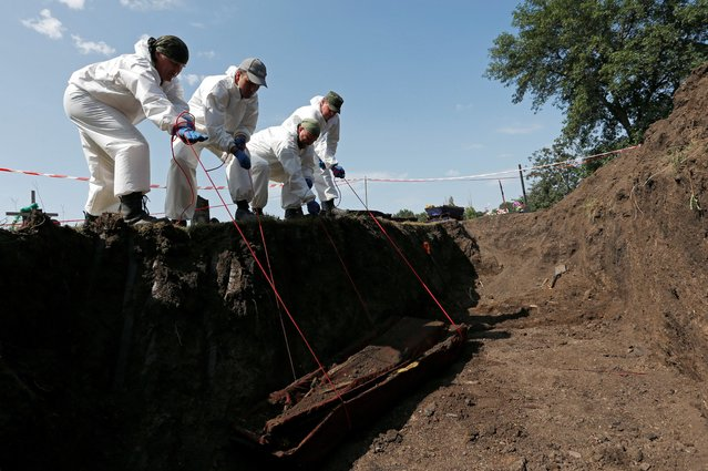 Volunteers lift a coffin from a mass grave during the exhumation of remains of civilians and military personnel killed during the military conflict in eastern Ukraine, at a cemetery in the rebel-controlled village of Snizhne (Snezhnoye) in Donetsk Region, Ukraine on August 19, 2021. (Photo by Alexander Ermochenko/Reuters)