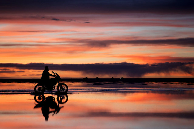 A local man rides his motorbike as the sun sets over the Salar de Uyuni of Uyuni Salt Flat during Day 7 of the 2014 Dakar Rally on January 11, 2014 in Uyuni, Bolivia.  (Photo by Dean Mouhtaropoulos/Getty Images)