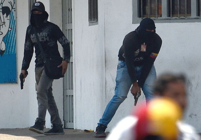 Armed members of a pro-Maduro militia attempt to disperse opposition demonstrators in San Antonio del Tachira, Venezuela on February 23, 2019. Venezuela's opposition leader Juan Gauido announced Saturday that a first shipment of humanitarian aid had entered Venezuela through its border with Brazil, deying a blockade by President Nicolas Maduro. (Photo by Federico Parra/AFP Photo)
