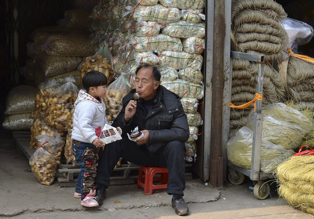 A man blows on a spoon to cool it off before feeding his grandson baked sweet potato as they wait for customers at a wholesale market in Hefei, Anhui province April 10, 2015. China's inflation data for March produced small positive surprises, but remained tepid, with little sign that Beijing's easing measures to date have significantly cut worrisome deflationary pressure. (Photo by Reuters/Stringer)