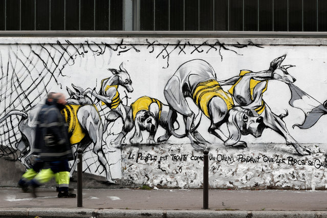 Peole walk past art work on a giant mural by French artist collective Black Lines celebrating the yellow vests movement in Paris, France, February 8, 2019. (Photo by Benoit Tessier/Reuters)