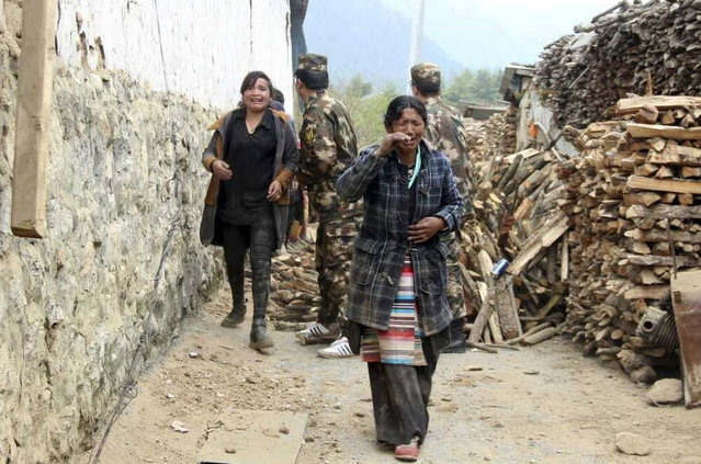 Residents cry as they walk past damaged houses to safer areas, after a 7.9 magnitude earthquake hit Nepal, in Gyirong county of Xigaze Prefecture, Tibet Autonomous Region, China, April 25, 2015. (Photo by Reuters/Stringer)