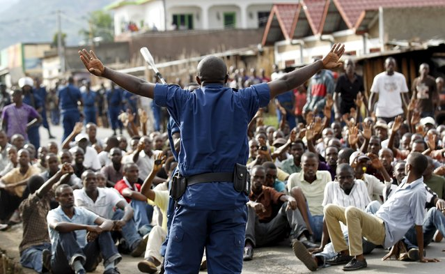 A riot police officer speaks to residents participating in street protests against the decision made by Burundi's ruling National Council for the Defence of Democracy-Forces for the Defence of Democracy (CNDD-FDD) party to allow President Pierre Nkurunziza to run for a third five-year term in office, in the capital Bujumbura, April 26, 2015. (Photo by Thomas Mukoya/Reuters)