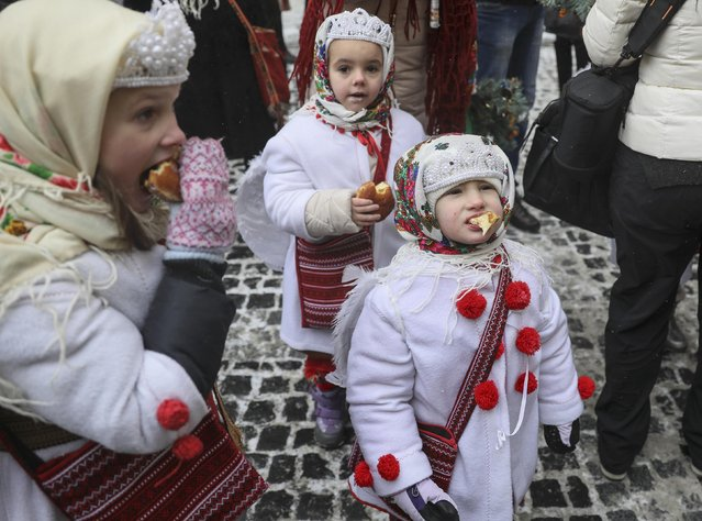 Children dressed in traditional costumes eat pampukhs, Ukrainian Christmas doughnuts, as they celebrate Orthodox Christmas in Lviv, Ukraine January 6, 2017. (Photo by Gleb Garanich/Reuters)