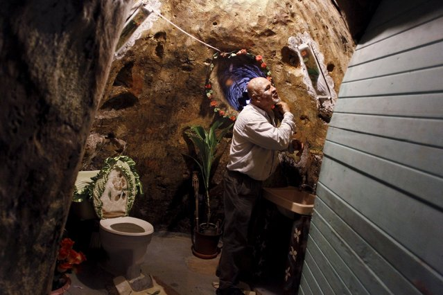 Manuel Barrantes shaves in a bathroom of his house he built underground in San Isidro de Perez Zeledon, Costa Rica, March 14, 2016. (Photo by Juan Carlos Ulate/Reuters)