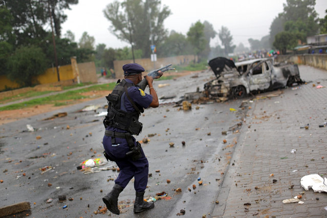 A member of the South African Police Service fires rubber bullets on striking community members in Zandspruit, an informal settlement west of Johannesburg, South Africa, 17 March 2016. Community members blocked and barricaded roads surrounding the settlement, after their illegal electricity connections where removed my Johannesburg Council workers almost a week ago. (Photo by Kevin Sutherland/EPA)