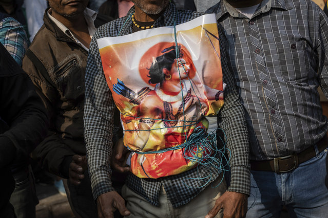 In this Sunday, December 9, 2018 photo, a supporter of Hindu-extreme political group Vishwa Hindu Parishad wears a poster of the Hindu god Ram during a rally in New Delhi, India. (Photo by Bernat Armangue/AP Photo)