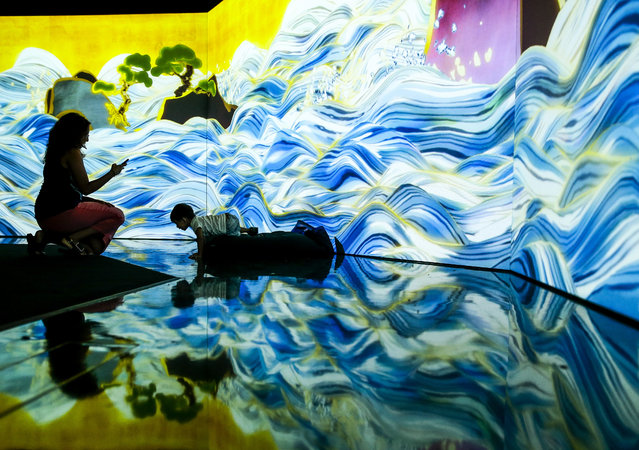 "A mother and child, reflected on the floor as they interact with a projection of waves titled ""100 Years Sea"" forming part of the installations at the Future World exhibit at the Art Science Museum in Singapore, March 18, 2016. The Future World exhibit is the ArtScience Museum's newest permanent exhibit and consists of 15 digital art installations developed in collaboration with Japanese art and technology collective teamLab. (Photo by Wallace Woon/EPA)"
