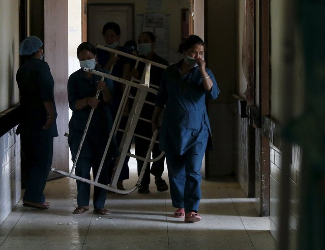 Health workers carry a hospital bed out of the maternity hospital which was damaged by the April 25 earthquake and is no longer in use in Kathmandu, Nepal, May 7, 2015. (Photo by Olivia Harris/Reuters)