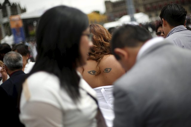 A tattoo is pictured on the back of a newly married bride after a mass wedding ceremony in which 2,016 couples participated, at Zocalo square in Mexico City, Mexico, March 19, 2016. (Photo by Edgard Garrido/Reuters)