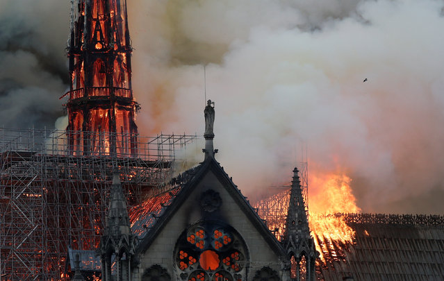 Smoke billows near scaffolding as fire engulfs the spire of Notre Dame Cathedral in Paris, France April 15, 2019. (Photo by Benoit Tessier/Reuters)