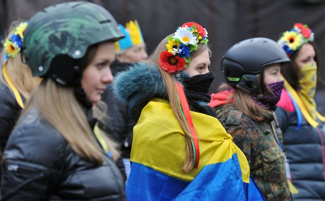 Activists of Maidan self-defence wearing helmets and crowns of flowers watch Kiev's communal services remove an opposition barricade on Grushevsky street in order to allow limited car traffic in accordance with an arrangement between anti-government opposition and the Ukrainian powers, in Kiev, on February 16, 2014. (Photo by Genya Savilov/AFP Photo)