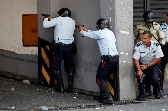 Police officers exchange fire with people shooting from inside a building housing the transport ministry in Caracas, April 30, 2019. (Photo by Carlos Garcia Rawlin/Reuters)