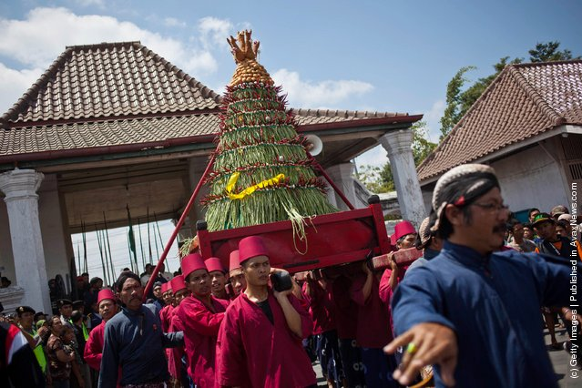 Volunteers of Kraton Palace, known as Abdi Dalem, carry Gunungan Lanang from Kraton Palace to the Great Mosque Kauman in Yogyakarta, Indonesia