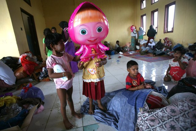 """An ethnic Rohingya young girl holds a balloon of Russian cartoon character """"Masha"""" at a temporary shelter in Lapang, Aceh province, Indonesia, Thursday, May 14, 2015. More than 1,600 migrants and refugees from Myanmar and Bangladesh have landed on the shores of Malaysia and Indonesia in the past week and thousands more are believed to have been abandoned at sea. (Photo by Binsar Bakkara/AP Photo)"""