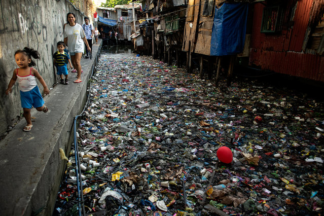 People walk along a canal polluted with plastic and garbage at the Estero de San Lazaro in Manila on March 22, 2019. Each year on March 22, World Water Day is observed around the world, focusing on the importance of fresh water and advocating for sustainable management of water resources. (Photo by Noel Celis/AFP Photo)
