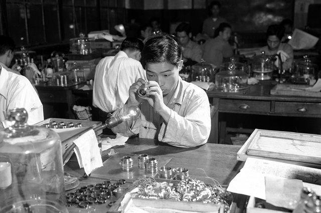 A lens is inspected at Tokyo's Nikon camera plant, on January 5, 1952. (Photo by Bob Schutz/AP Photo via The Atlantic)