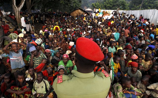 A Tanzanian policeman watches over as Burundian refugees gather on the shores of Lake Tanganyika in Kagunga village in Kigoma region in western Tanzania, to they wait for MV Liemba to transport them to Kigoma township, May 17, 2015. (Photo by Thomas Mukoya/Reuters)