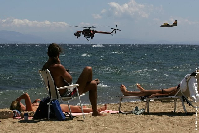 Sunbathing tourists watch a helicopter as it collects sea water to dowse fire, as wild fires burn in the suburbs