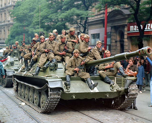 Soviet Army soldiers sit on their tanks in front of the Czechoslovak Radio station building in central Prague during the first day of Soviet-led invasion to then Czechoslovakia on August 21, 1968. (Photo by Libor Hajsky/Reuters)