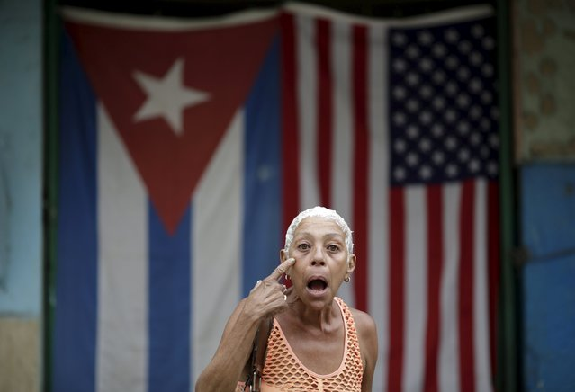 "Concha gestures while posing for a photograph in front of the Cuban and U.S. flags in Havana, March 25, 2016. Regarding Obama's historic visit to the island, Concha said ""A life struggle"". (Photo by Ueslei Marcelino/Reuters)"