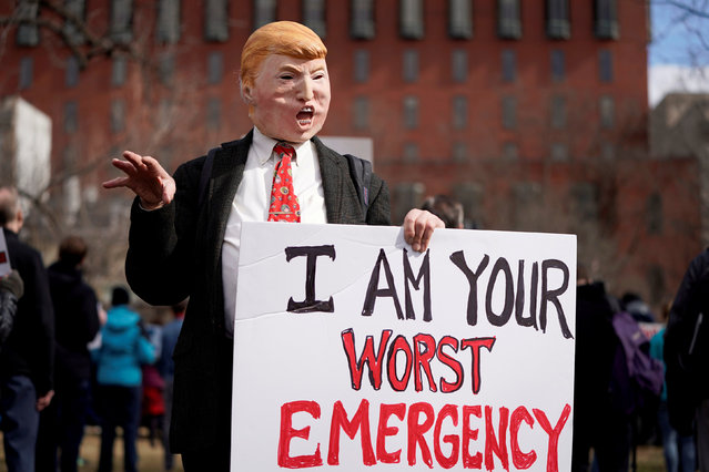 A protester wearing a mask depicting U.S. President Donald Trump holds a sign during a demonstration against Trump on President's day near the White House in Washington, U.S., February 18, 2019. (Photo by Joshua Roberts/Reuters)