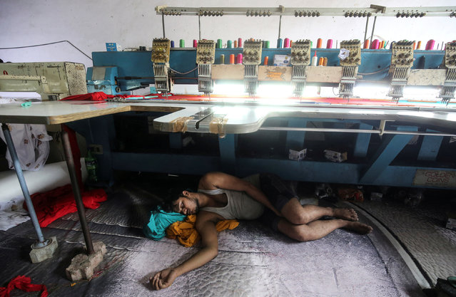 A worker sleeps underneath an embroidery machine at a workshop in Mumbai, India, May 31, 2019. (Photo by Francis Mascarenhas/Reuters)