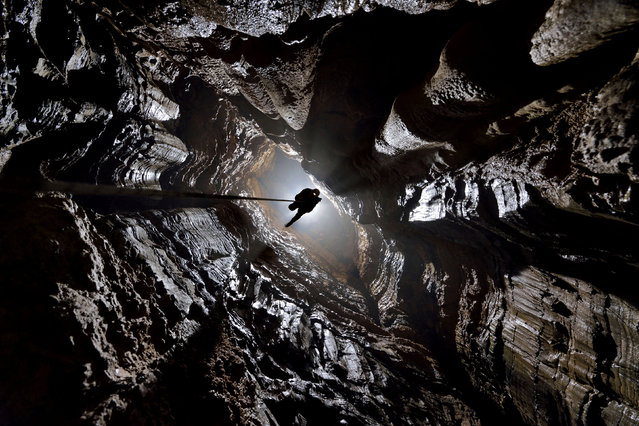 Climbing the rope up a vertical section of cave known as a pit in Xinu Attic. (Photo by Robbie Shone/Caters News/ImagineChina)